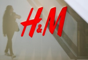 A woman is reflected next to logo of H&M fashion retailer in newly opened Mall of Berlin shopping centre in Berlin